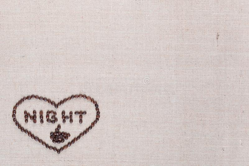 Night in heart sign from coffee beans isolated on linea texture, aligned bottom left royalty free stock photos