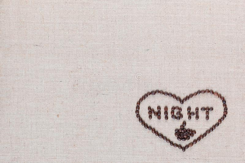 Night in heart sign from coffee beans isolated on linea texture, aligned bottom right stock photo