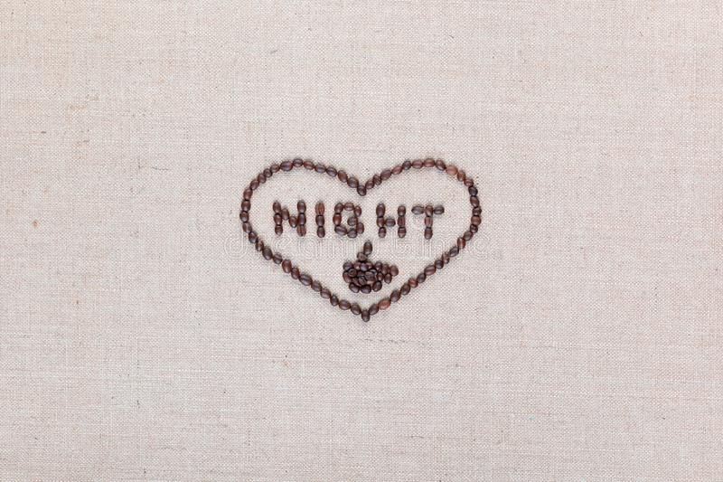 Night in heart sign from coffee beans isolated on linea texture, aligned in center royalty free stock photography