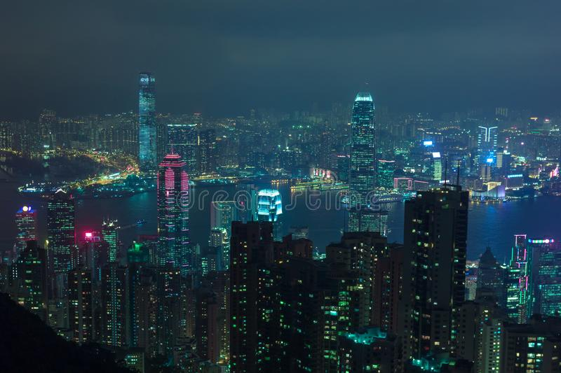 Night Hong Kong skyscrapers with cyberpunk lights. Night scene of Hong Kong city taken from Victoria Peak showing lit up skyscrapers and Victoria Harbor. Lights stock photography