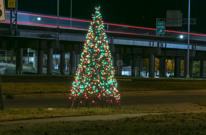 Night image of a Lighted Christmas Tree next to Interstate 20. With traffic light trails stock image