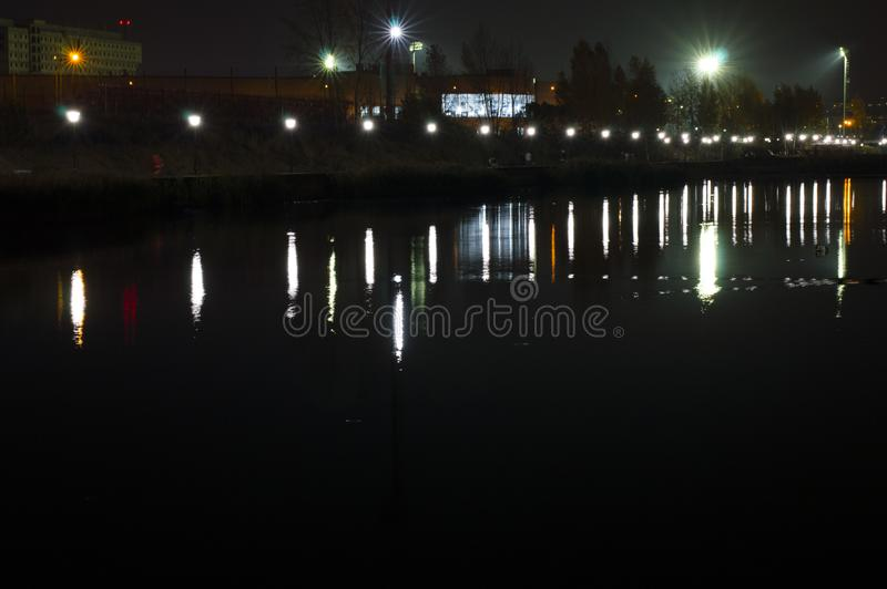 Night lake in the city, the reflection of the light of lanterns and street illumination lights. Russia stock images