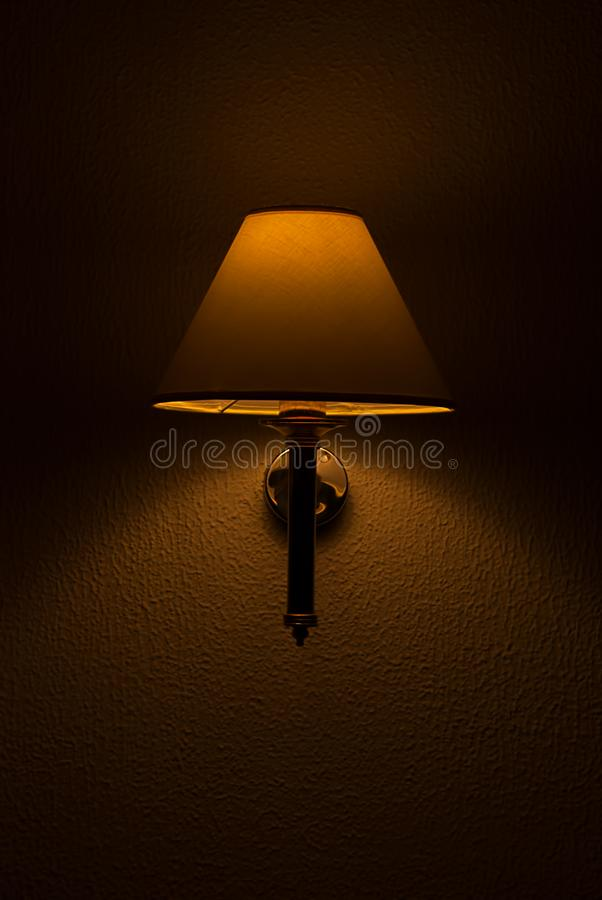 Night lamp with a muted light on a relief wall stock photography