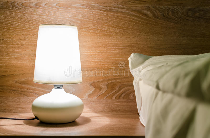 Night lamp on a nightstand illuminating the bed royalty free stock photography