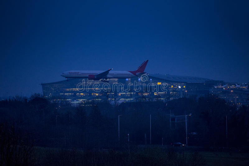 Night Landing at Heathrow airport. Air India Boeing 777 landing at night over lit up Terminal 5 at Heathrow Airport royalty free stock images