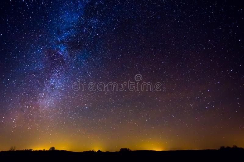 Night landscape with colorful milky way and yellow light in the horizon stock photography