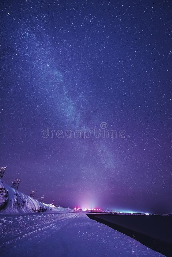 Night landscape with colorful Milky Way and yellow light at mountains. Starry sky with hills at summer. Beautiful Universe. Space royalty free stock images