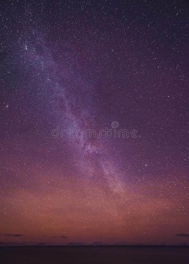 Night landscape with colorful Milky Way and yellow light at mountains. Starry sky with hills at summer. Beautiful Universe. Space royalty free stock photo