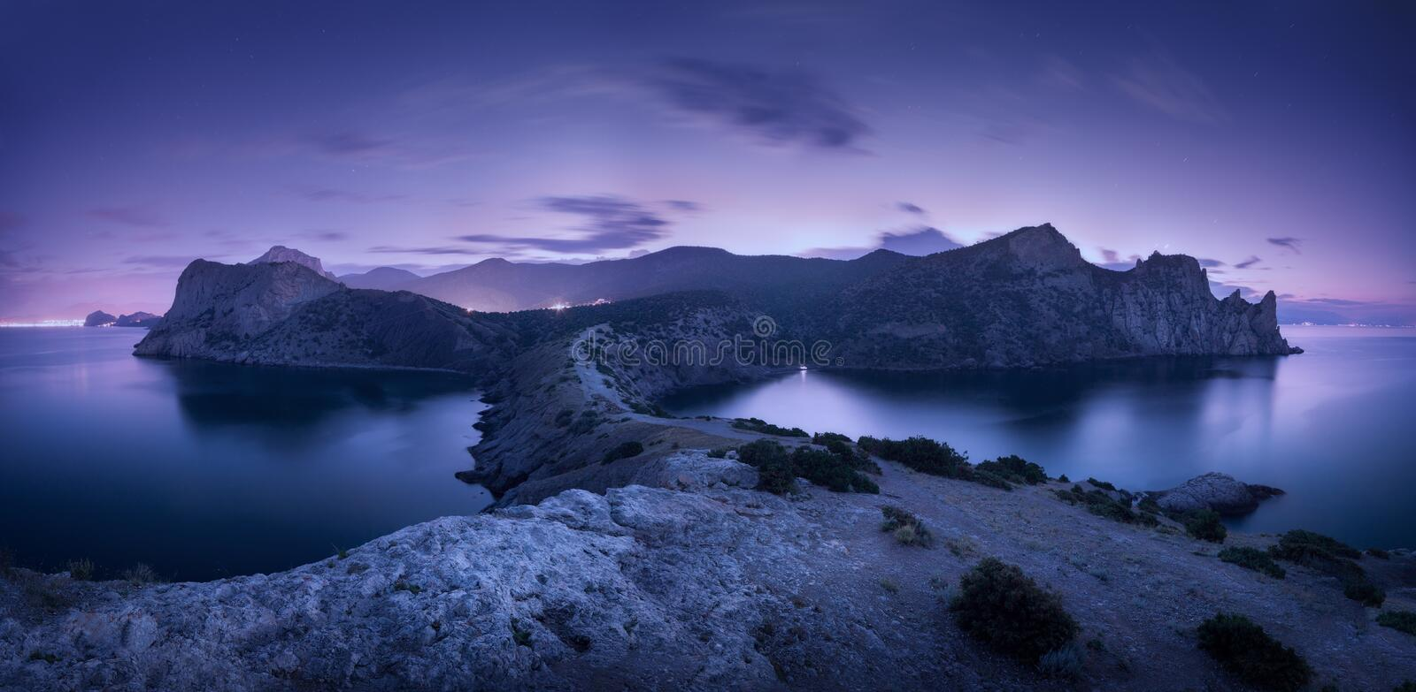 Night landscape with mountains, sea and starry sky. Dusk stock photos
