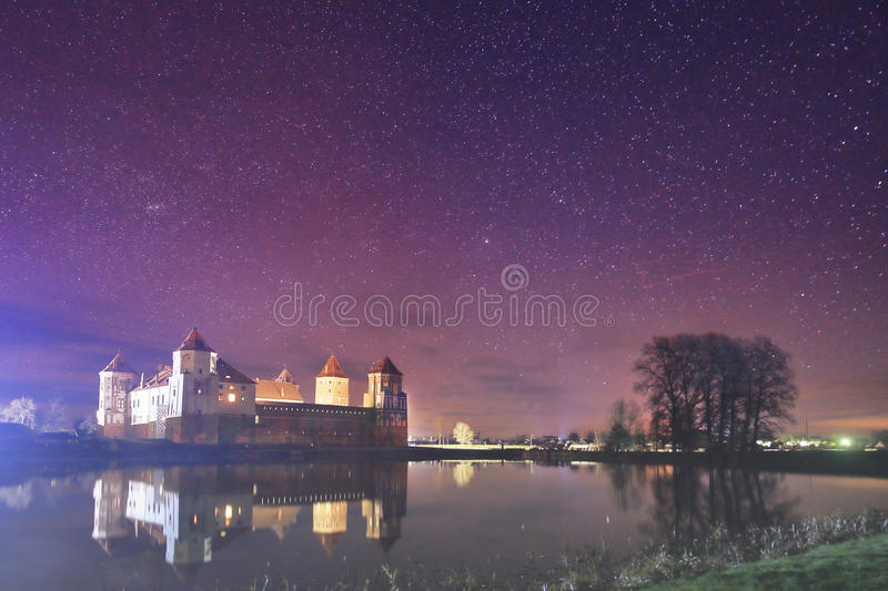 Night landscape of the old castle in the background of the starry sky and the lake. royalty free stock images