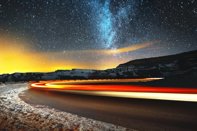 Night landscape. Night sky with a north hemisphere Milky Way and stars. The night road illuminated by the car winds with. A serpentine and leaves in a distance stock image