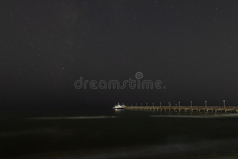 Night landscape. Small pleasure boat moored to a pier near the sea coast. royalty free stock photo