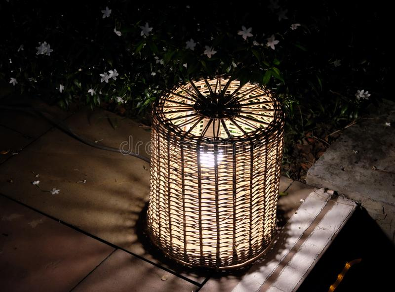 Night lantern woven from a rod. Bush with small white flowers. Night scene.  royalty free stock image