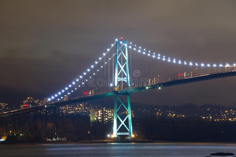 Night long exposure shot of bridge with glowing lights. Nightlife atmosphere of Vancouver downtown at night with Lions Gate bridge royalty free stock image