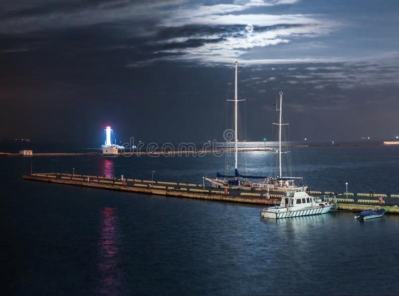 Night marina with yachts and lighthouse royalty free stock photos