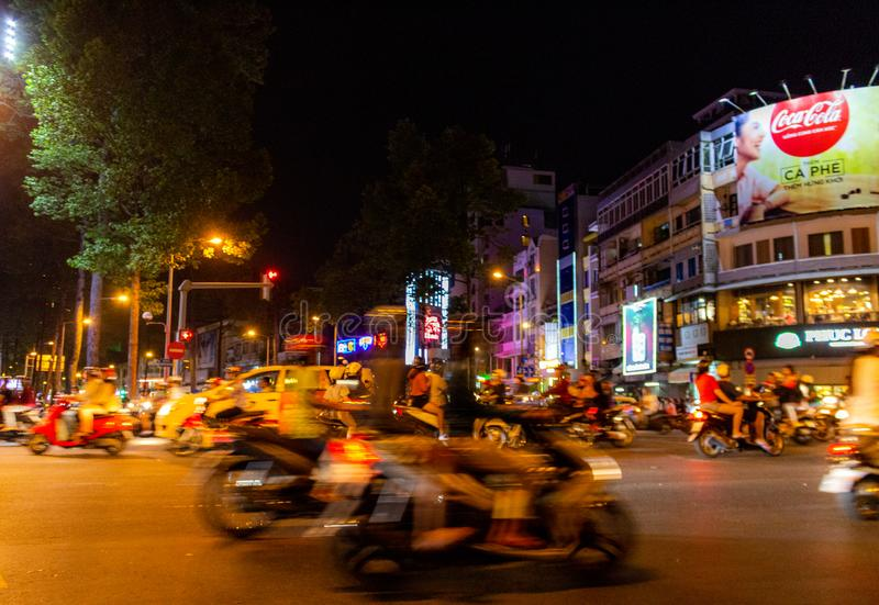 Night motorbike traffic Saigon Vietnam. Ho Chi Minh City, Vietnam - May 13, 2018: Motorbikes traffic at a intersection in central Saigon by night stock photography