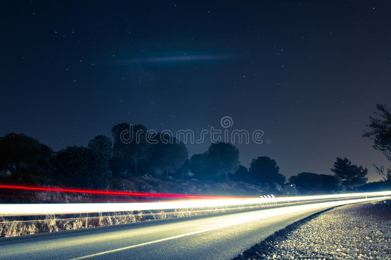 Night mountain road with car trails stock image