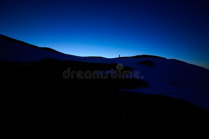 Night mountains landscape view with dark deep blue sky stars and sunset dusk evening lightning on the horizon, black hills and one. Lonely man silhouette on royalty free stock photos
