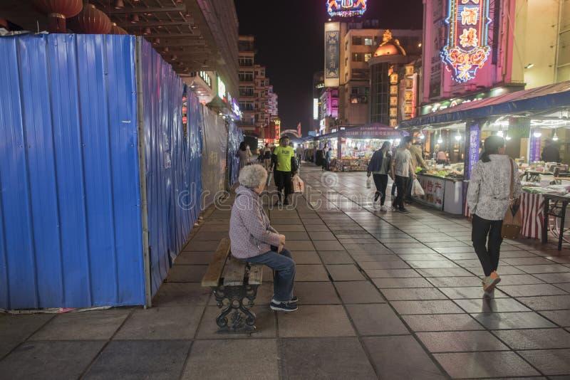 An elderly woman resting on a stone stool. At night, Nanjing Gulou District, Jiangsu Province, Hunan Road Pedestrian Street, an elderly woman sitting on a stone royalty free stock photos