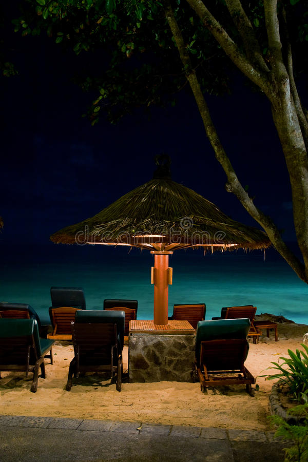 Night paradise beach with deck chair and umbrella. In Bali stock photo