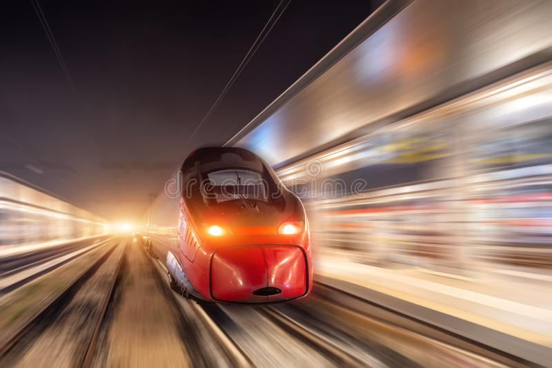 Night passenger high-speed train passing the station in the city.  stock photography
