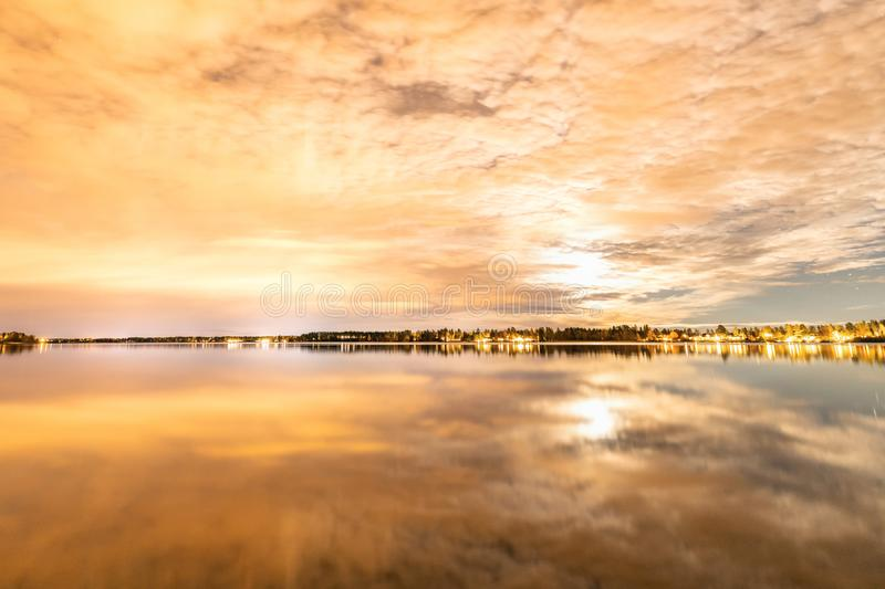 Night photo of clouds mirror reflected at Swedish countryside lake, moon shines behind clouds and gives unreal colors. Northern Sweden royalty free stock images