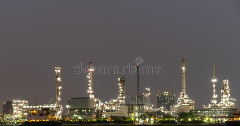 Night photo crude oil refinery plant and many chimney with petrochemical tanker or cargo ship at coast of the river with colorful royalty free stock photos
