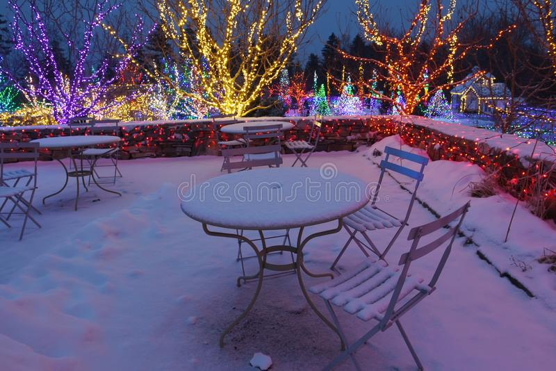 Night photo. Decorated with colored lights and garlands snow-covered garden. Cafe outside in the snow. The atmosphere of winter holidays and magic royalty free stock images