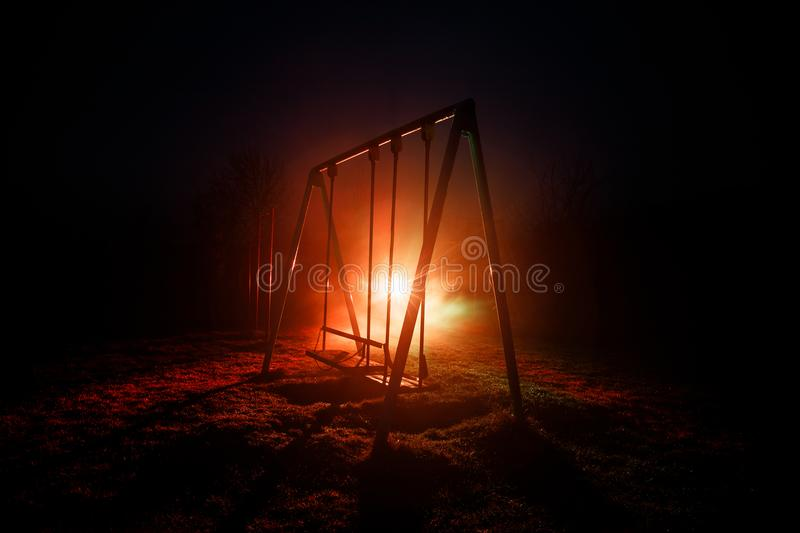 Night photo of metal swing standing outdoor at night time with fog and surreal toned light on background. Nobody there. stock photography