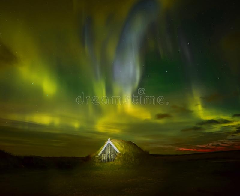 Night photo. Northern lights and a small house in the land overgrown with grass. Iceland. stock photo