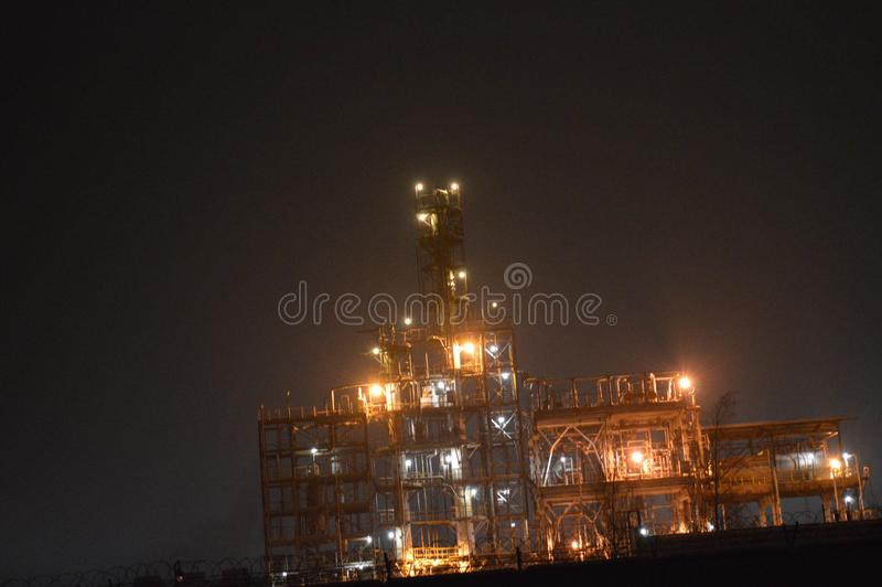 Night photo of an oil refinery, a petrochemical plant through a fence. With a barbed wire. Technological installation for the production of fuel royalty free stock photography