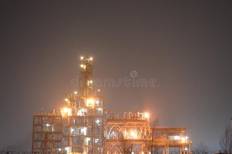 Night photo of an oil refinery, a petrochemical plant. Through a fence with a barbed wire. Technological installation for the production of fuel royalty free stock photos