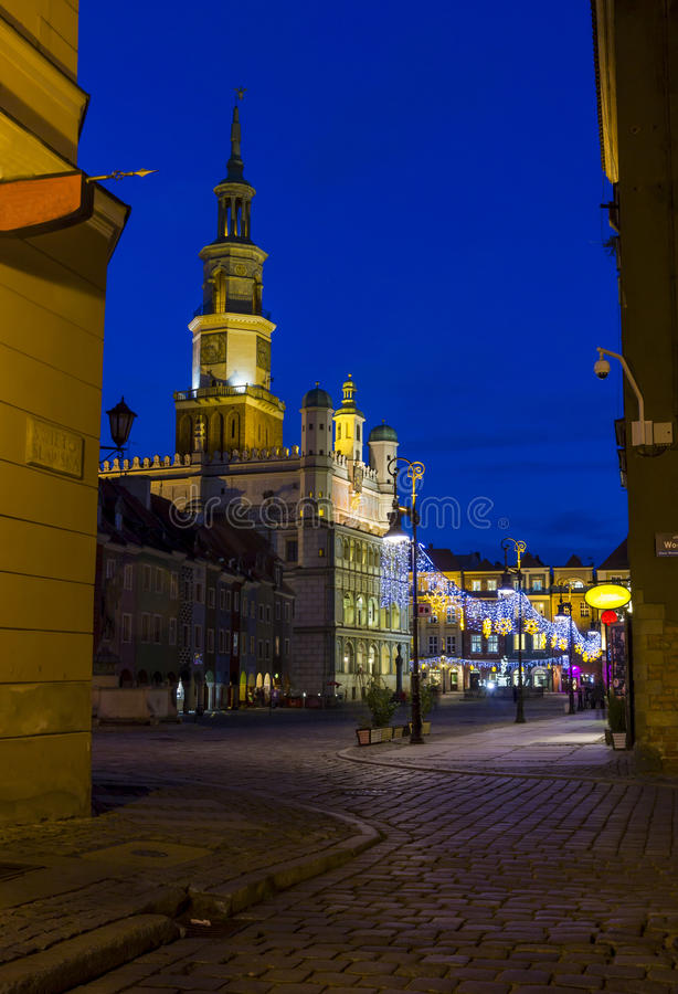 Night photo of an old town square and city hall in Poznan, Poland. From one of cobbled, neighbouring streets stock photos