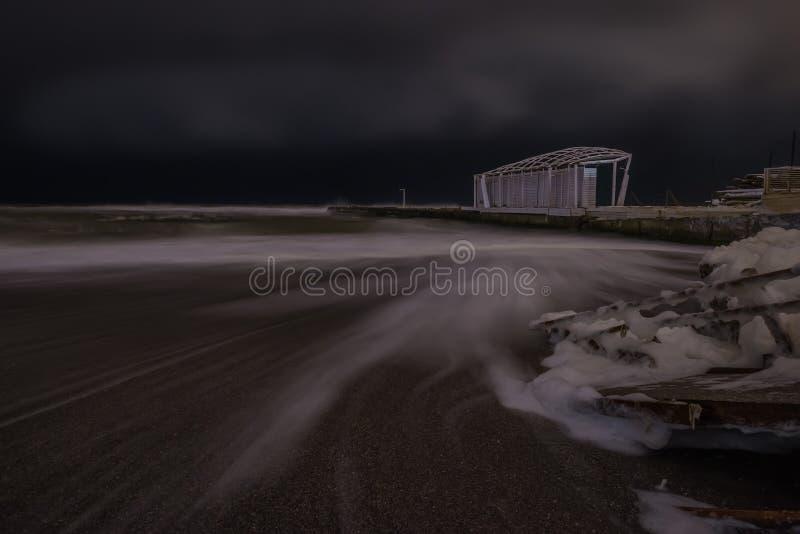 Night photo of the severe winter sea. Long exposure. stock image