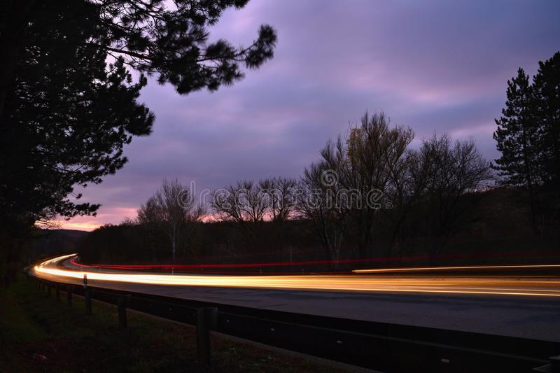 Night photo traffic on the road. Evening landscape with cars. Cars with lights and blurred color lines. Night photo traffic on the road. Evening landscape with stock photos