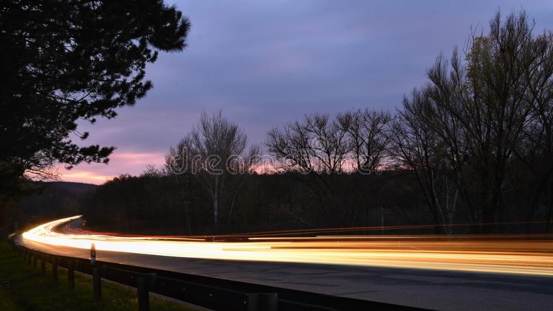 Night photo traffic on the road. Evening landscape with cars. Cars with lights and blurred color lines. Night photo traffic on the road. Evening landscape with royalty free stock image