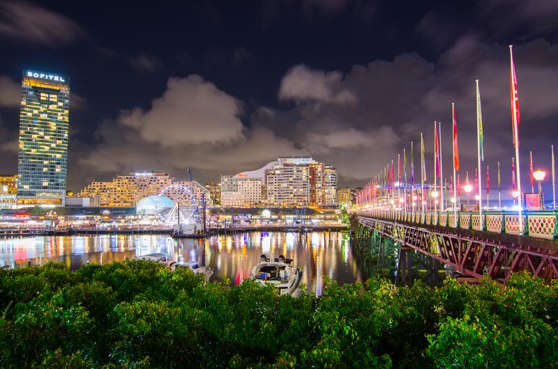 Night photography of Cockle Bay and Pyrmont bridge at Darling Harbour cityscape with dramatic cloudy sky view. royalty free stock photography