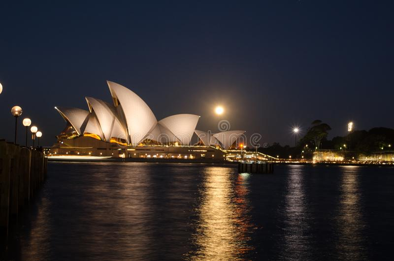 Night photography of Full moon above Sydney Opeara house with its shadow on ocean water surface. SYDNEY, AUSTRALIA. – On July 9, 2017. - Night stock photography