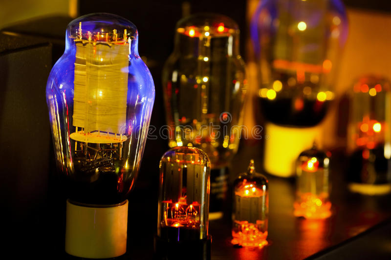 Night pictures of hi fi vacuum tubes amplifier Old-fashioned electronic device amplifier with glowing bulb diode lamp for sound r. Eproduction . Focus only lamp stock image