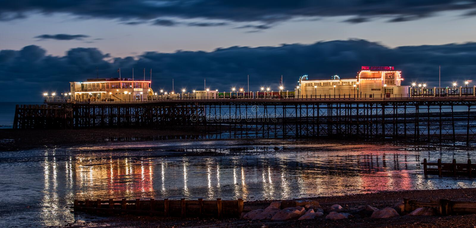 Night Pier with light reflections at low tide stock photo