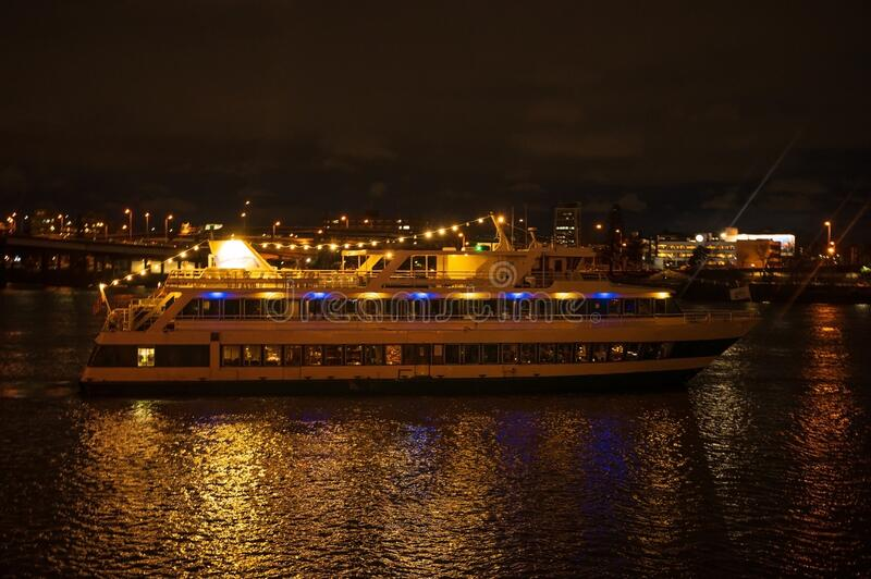 Night pleasure boat, or yacht for a walk with people. Night city with a river and a big boat.  royalty free stock photo
