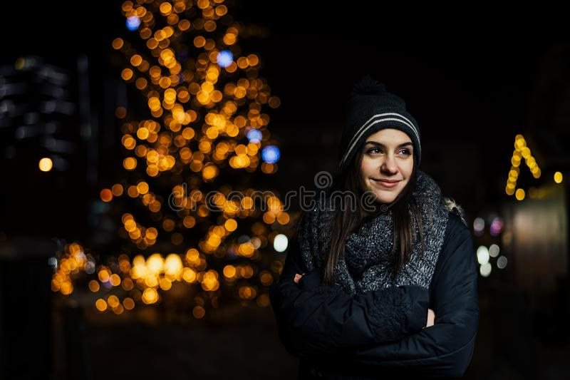 Night portrait of a beautiful brunette woman smiling enjoying winter in park.Winter joy.Winter holidays.Positive emotions. royalty free stock images