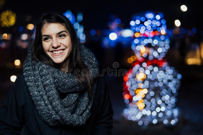 Night portrait of a beautiful brunette woman smiling enjoying winter in park.Winter joy.Winter holidays.Positive emotions. Happiness royalty free stock photography