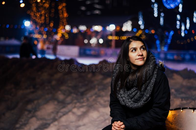 Night portrait of a beautiful brunette woman smiling enjoying winter in park.Winter joy.Winter holidays.Positive emotions. Happiness stock photography
