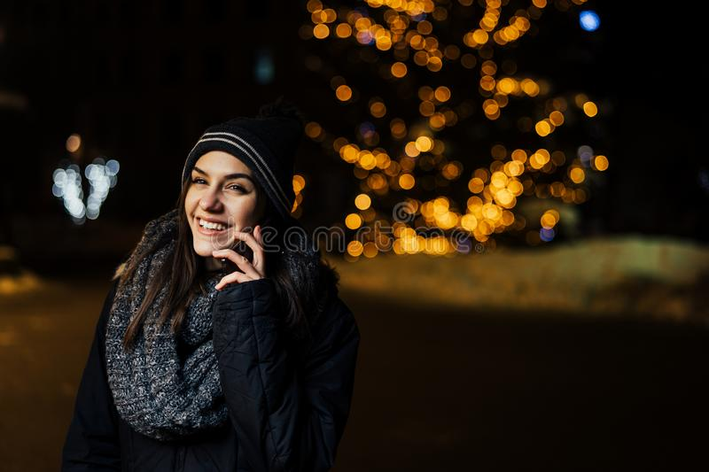 Night portrait of a beautiful brunette woman using smartphone during cold winter in park.Winter joy.Winter holidays.Positive. Emotions.Communication royalty free stock image