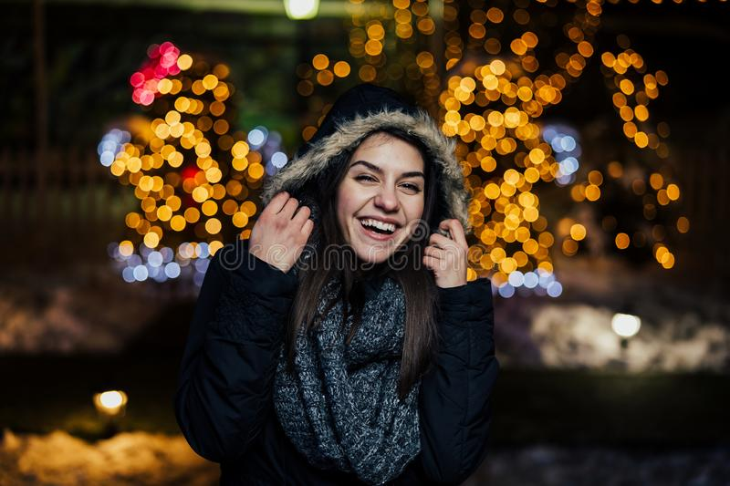 Night portrait of a beautiful happy woman smiling enjoying winter and snow outdoors.Winter joy.Winter holidays.Positive emotions. Happiness royalty free stock photography
