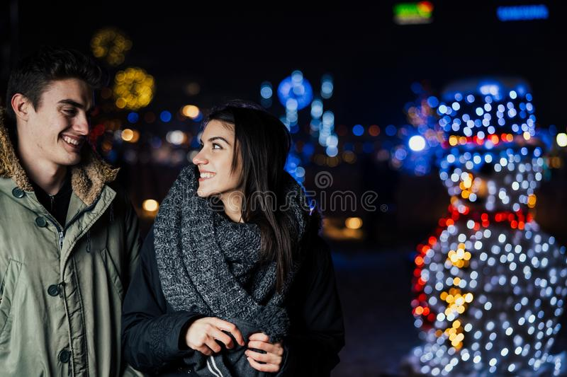 Night portrait of a happy couple smiling enjoying winter and snow aoutdoors.Winter joy.Positive emotions.Happiness. Concept stock photography