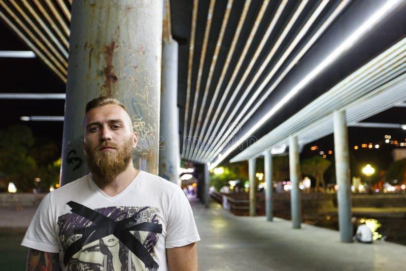 Night portrait of a street bearded man drug seller gang member bandit. Hiding behind a column royalty free stock photo