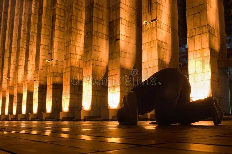 Night prayer. Man prays on night at golden mosque