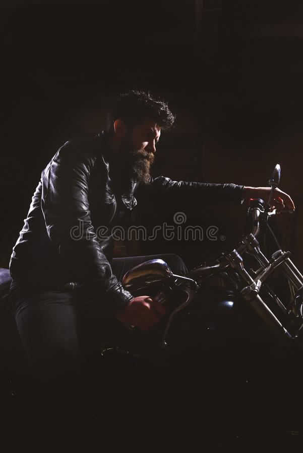 Night racer concept. Macho, brutal biker in leather jacket riding motorcycle at night time, copy space. Man with beard. Biker in leather jacket sitting on royalty free stock photo